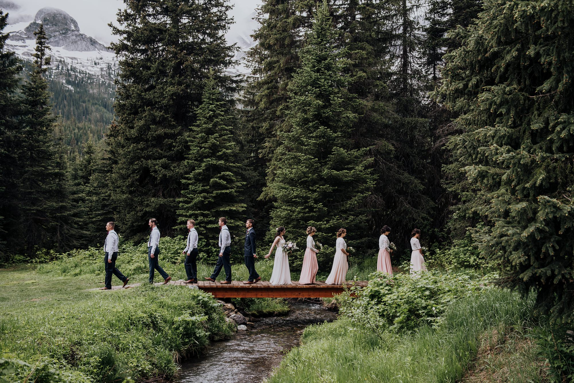 bride and groom with bridal party in the forest at island lake lodge wedding