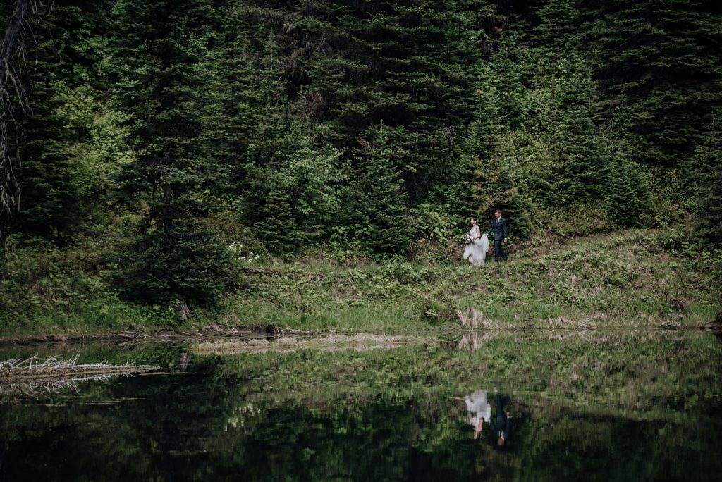 bride and groom walk in the forrest at island lake lodge wedding