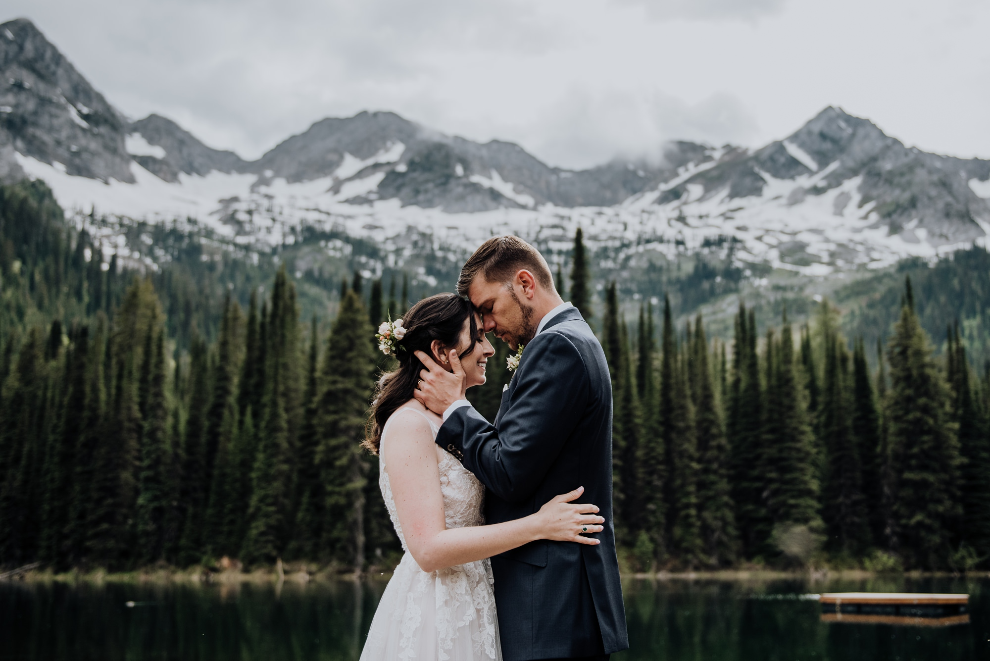 bride and groom at lake during classic, modern mountain wedding at island lake lodge wedding captured by calgary wedding photographer