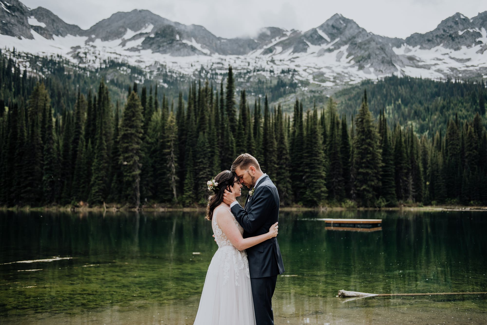 bride and groom at lake during classic, modern mountain wedding at island lake lodge wedding captured by calgary wedding photographer