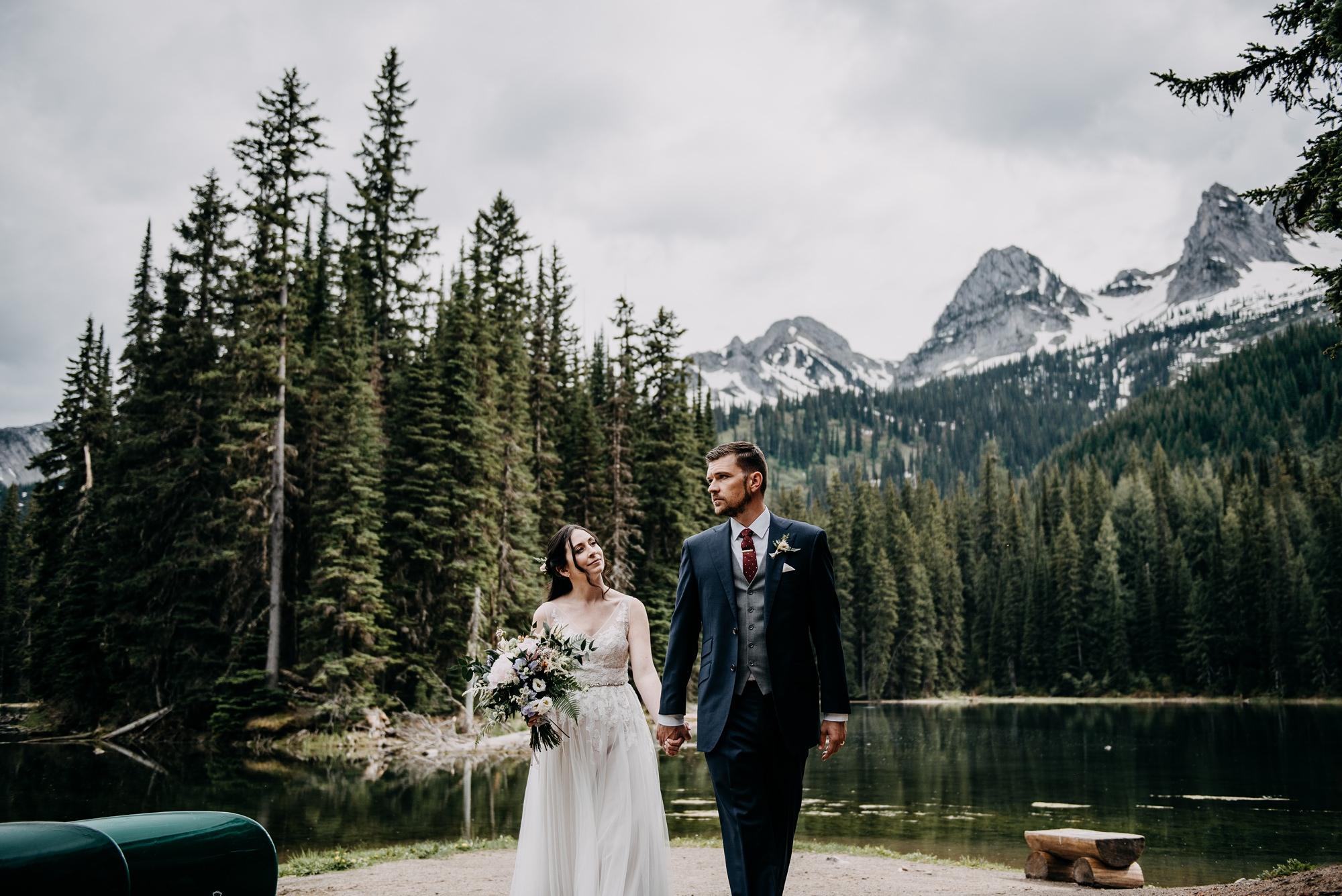 bride and groom walking at lake in classic modern island lake lodge wedding