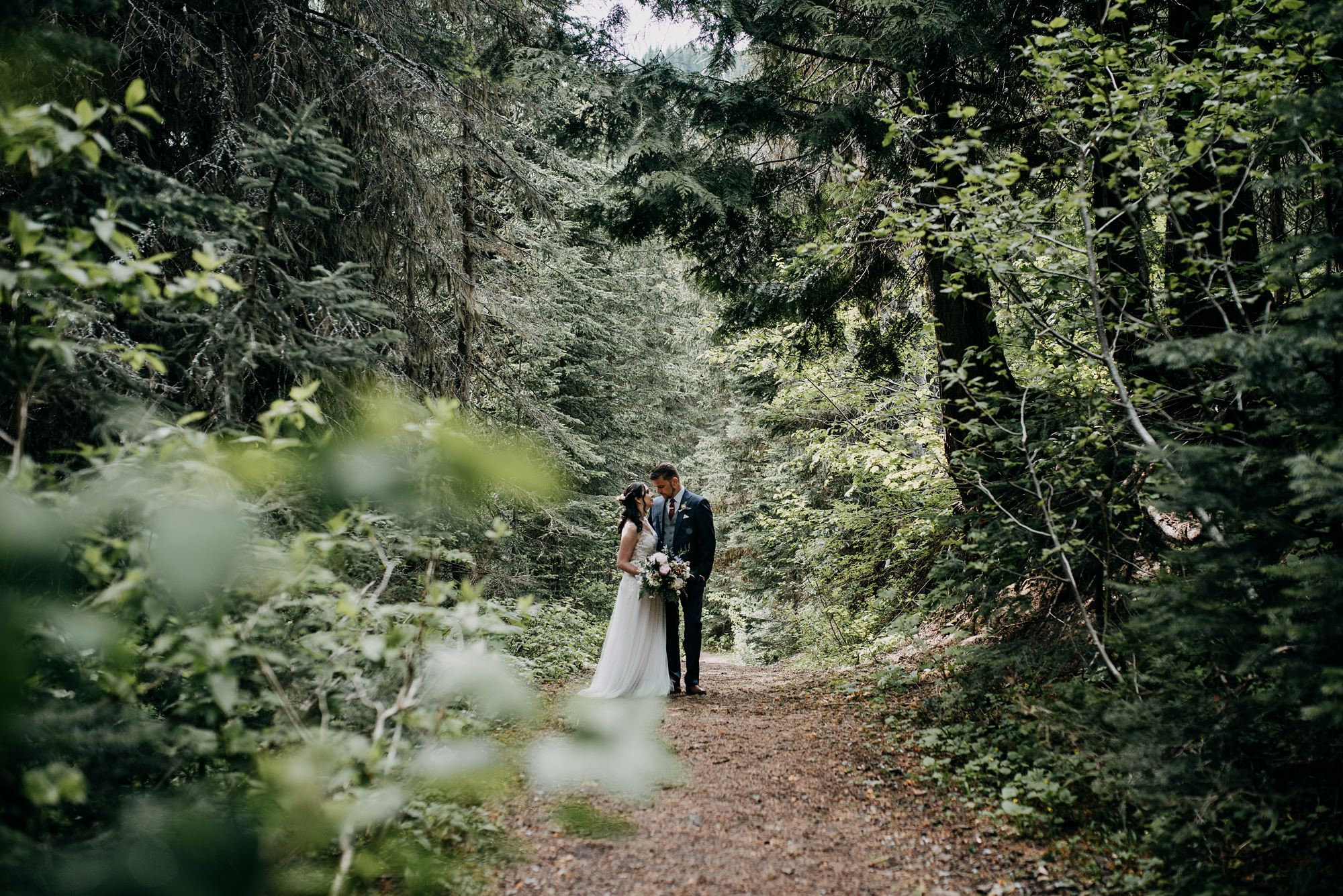 bride and groom in the forest at island lake lodge wedding