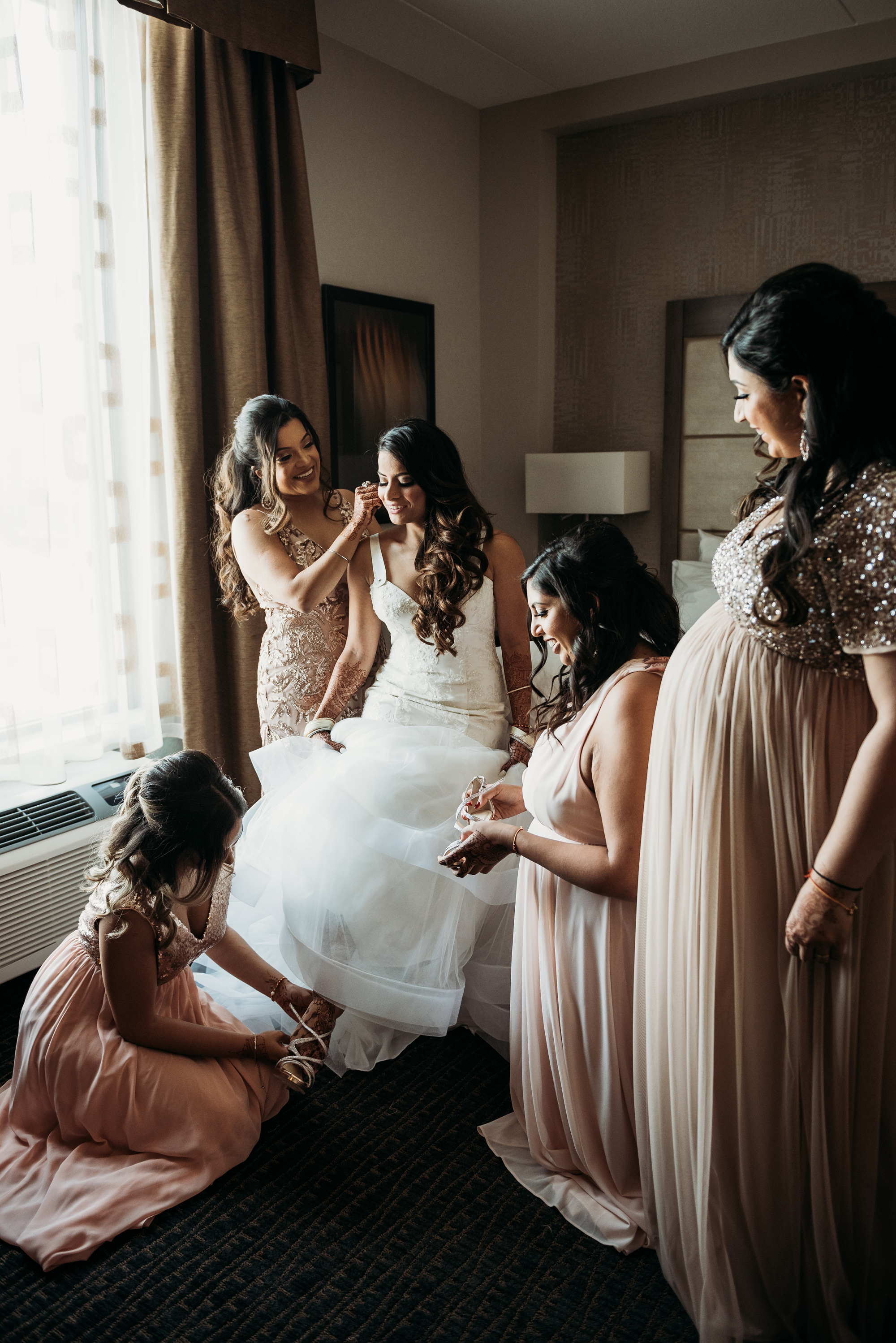 indian bride getting ready with bridesmaids before outdoor calgary wedding ceremony