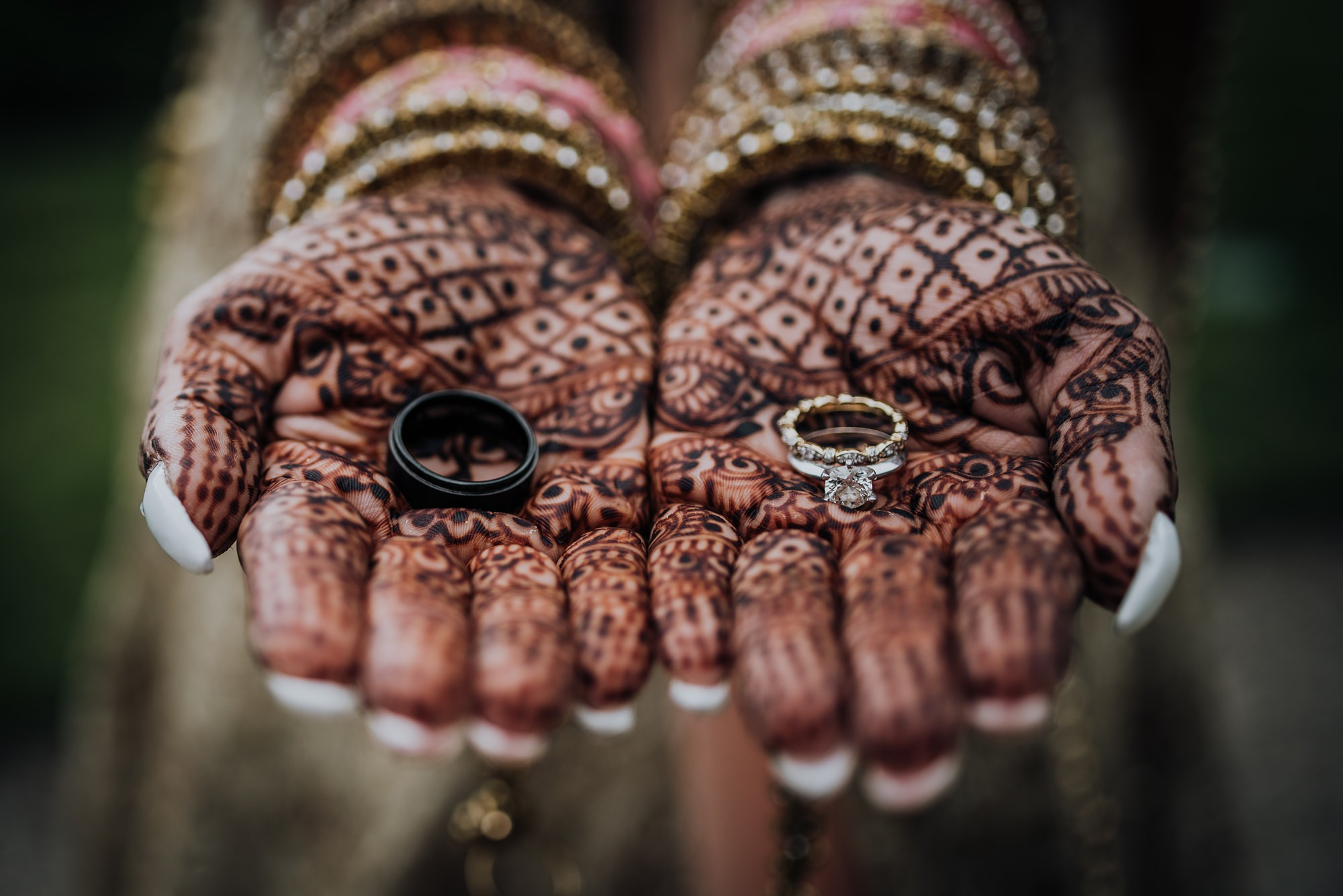 detail shot of wedding rings in the mendhi hands of indian bride during calgary indian wedding photography