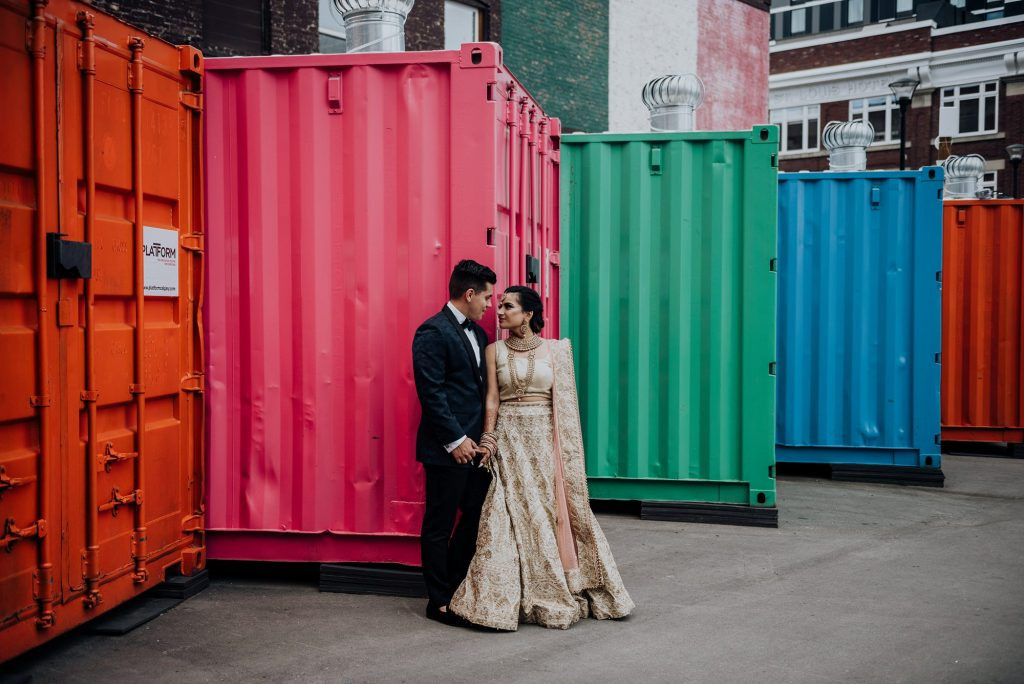 indian bride and groom standing infront of colourful containers during wedding portraits