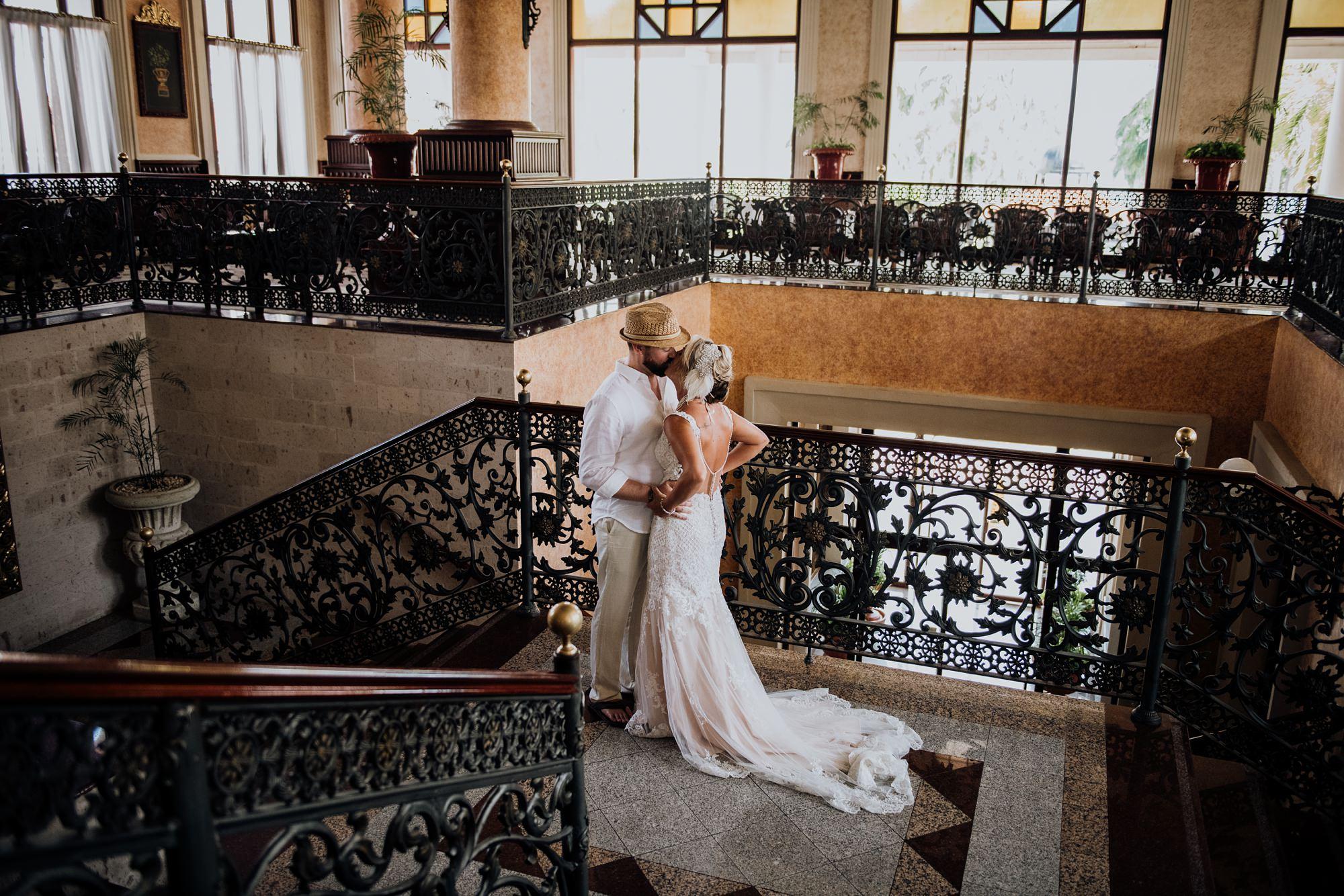 bride and groom kiss elegant foyer Riu Palace Riviera Maya