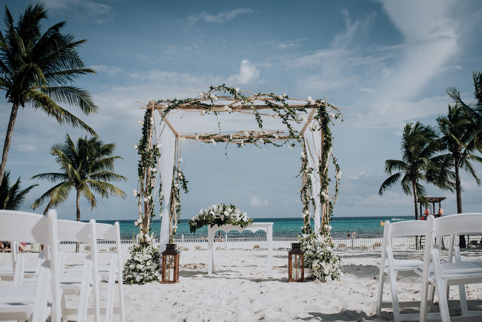 white wedding florals and arbour on beach ceremony