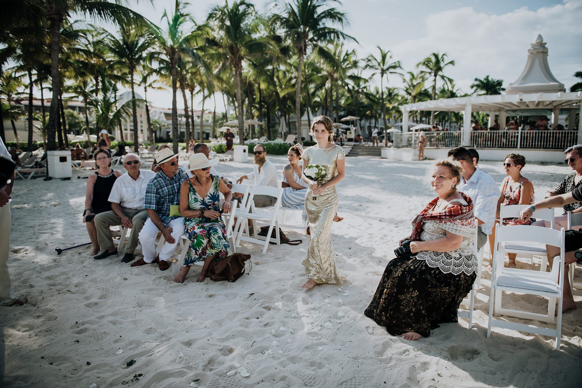 bridesmaid walking into wedding ceremony on beach