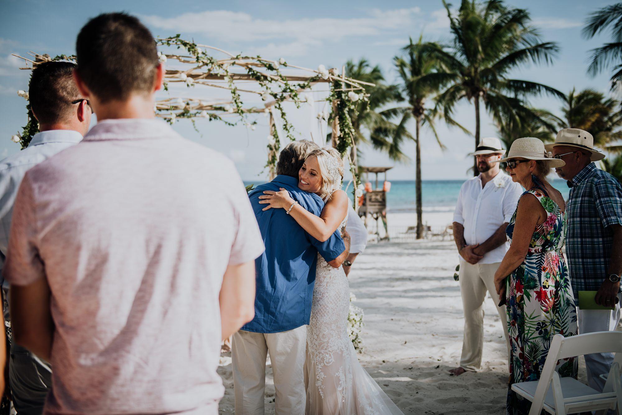 bride and father hug beach wedding ceremony bride and groom exit beach wedding ceremony at mexico hotel Riu Palace Riviera Maya