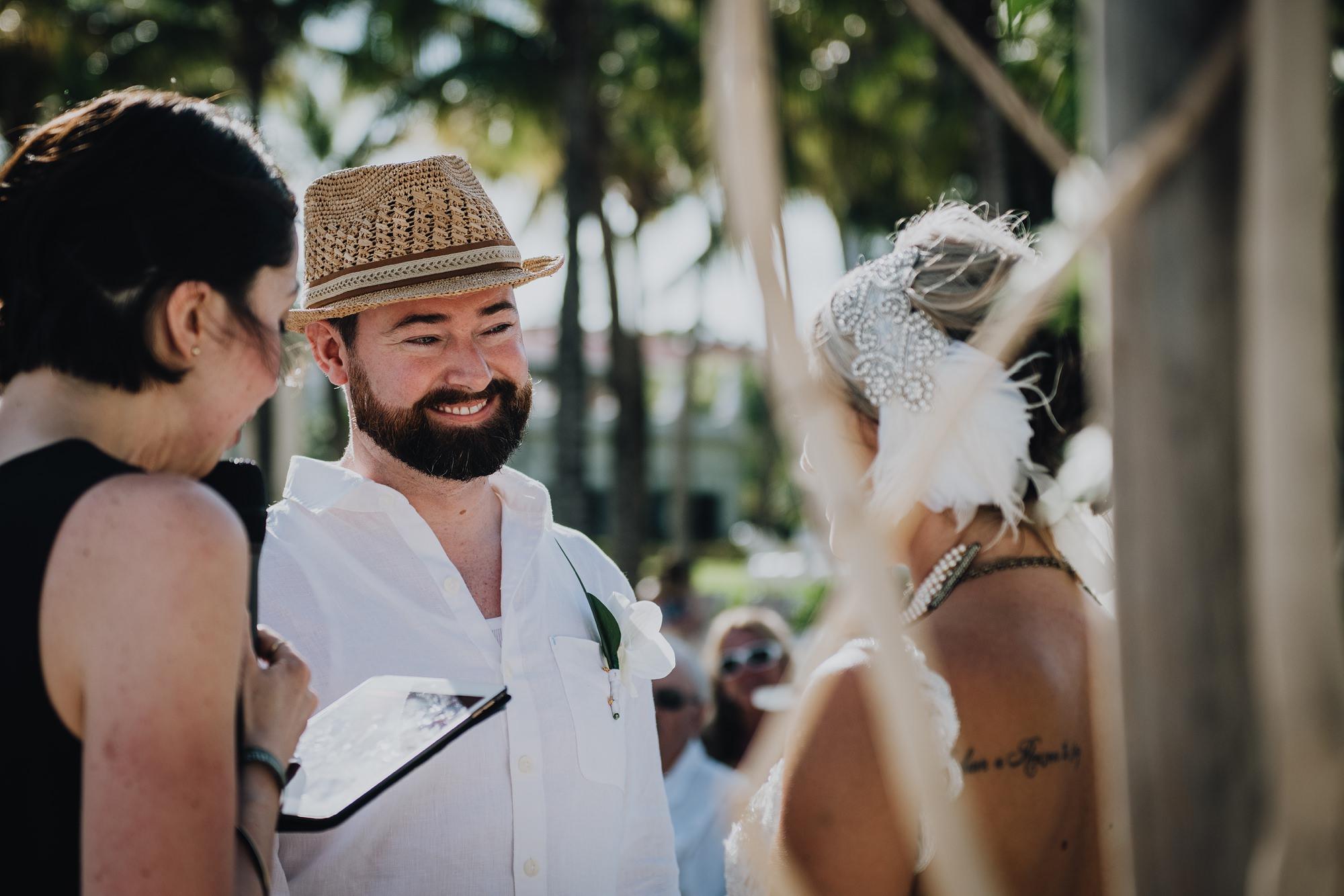 groom looking at bride during beach wedding ceremony