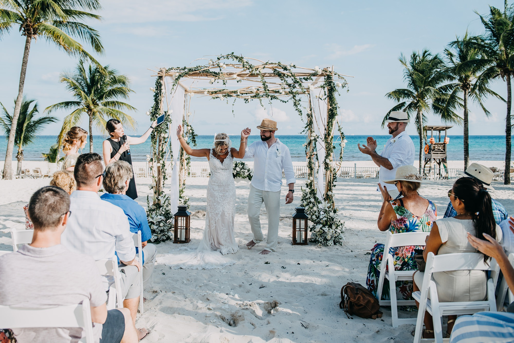 bride and groom exit beach wedding ceremony at mexico hotel Riu Palace Riviera Maya