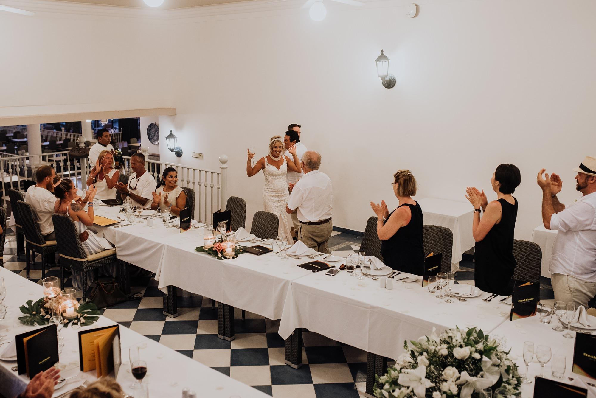 bride and groom enter out door beach wedding reception at Riu Palace Riviera Maya