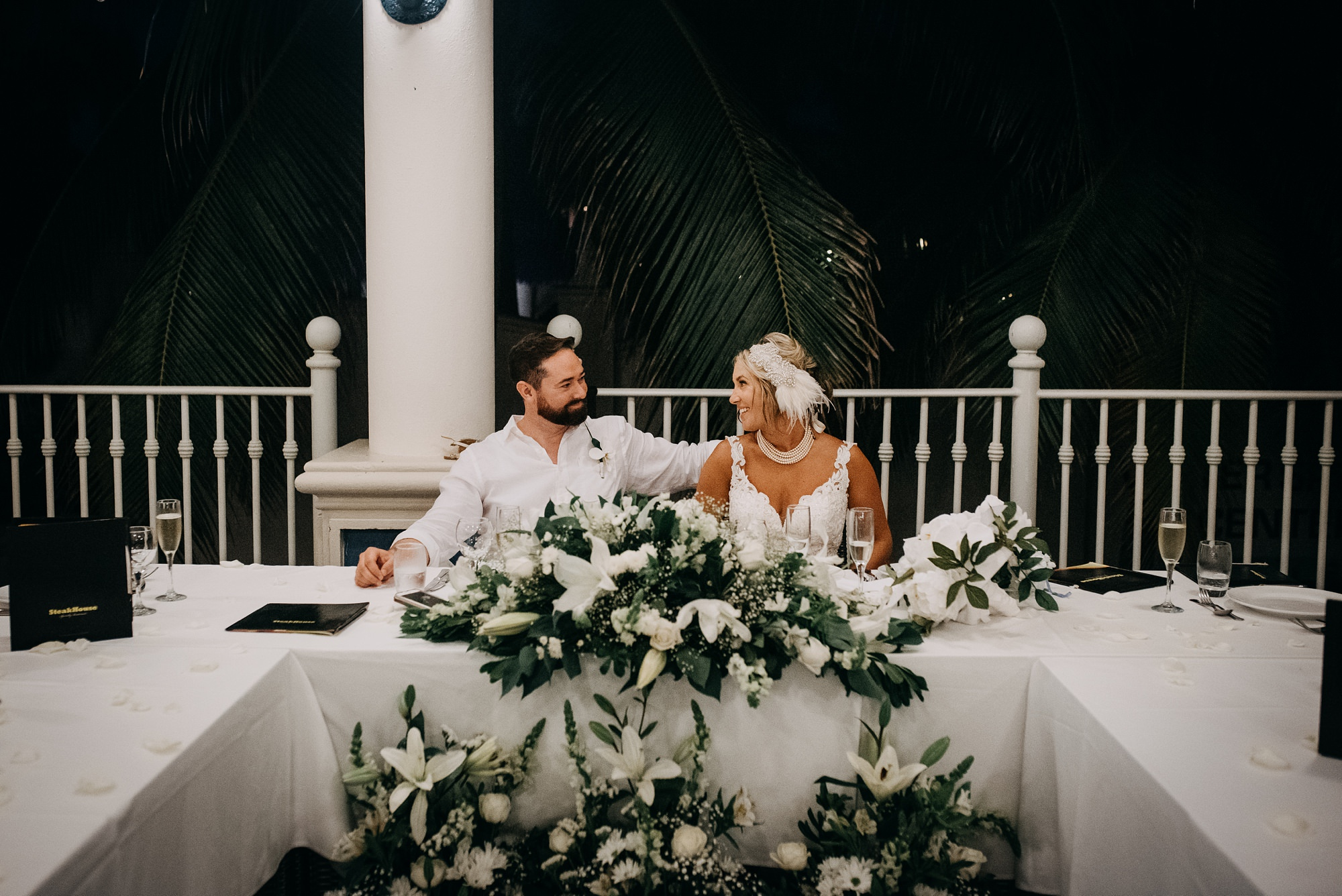 bride and groom at Riu Palace Riviera Maya wedding reception with neautral florals