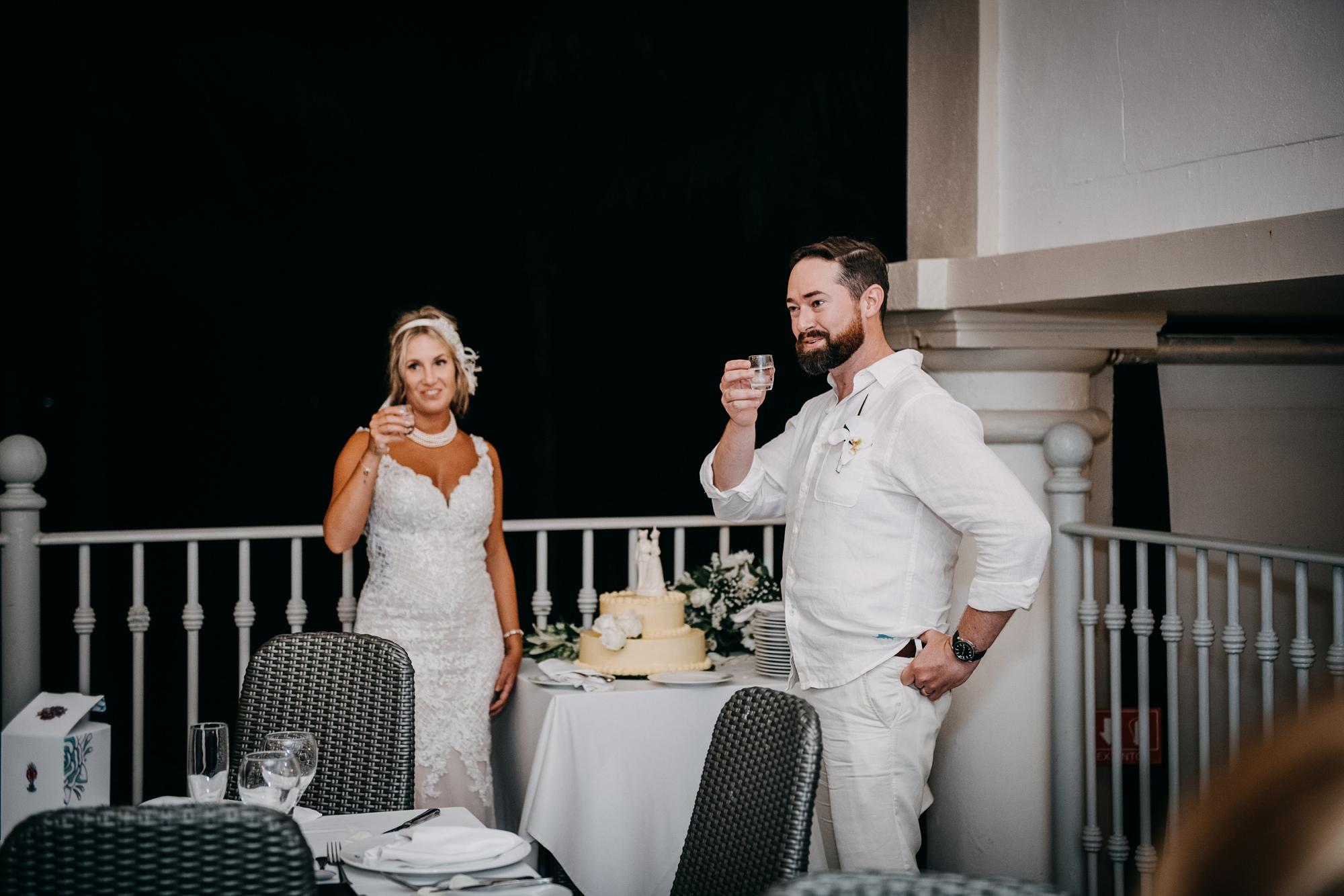 bride and groom sharing shots at outdoor Riu Palace Riviera Maya wedding reception
