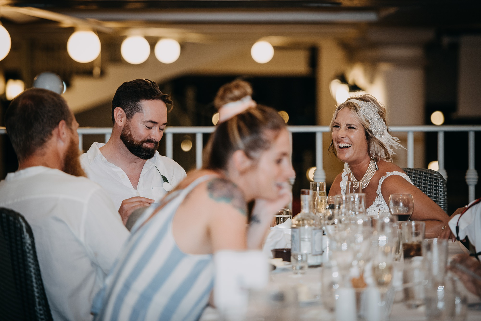 bride and groom laughing at outdoor wedding reception on beach