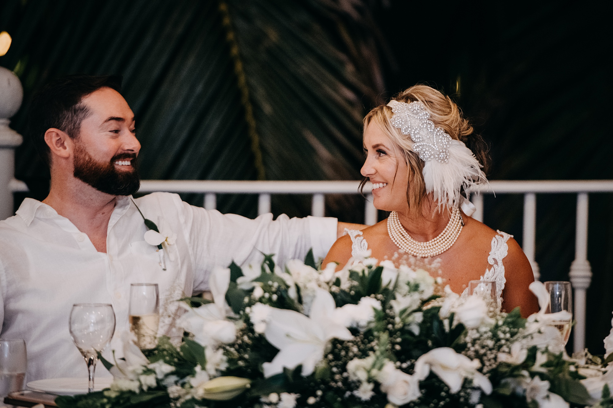 bride and groom at outdoor reception with tropical florals