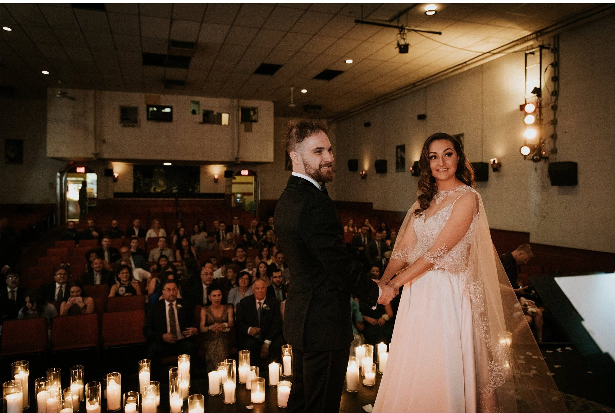 bride and groom on stage during plaza theatre ceremony in kensington