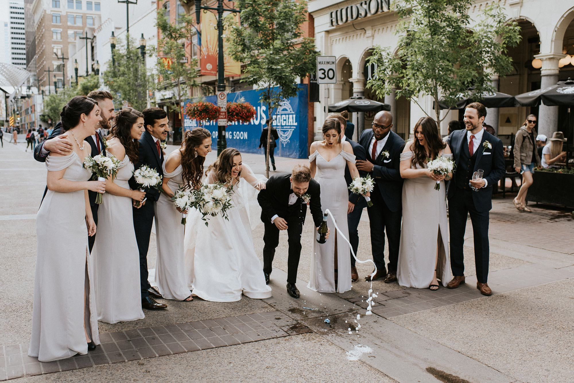 bridal party popping champagne on stephen ave in downtown calgary wedding