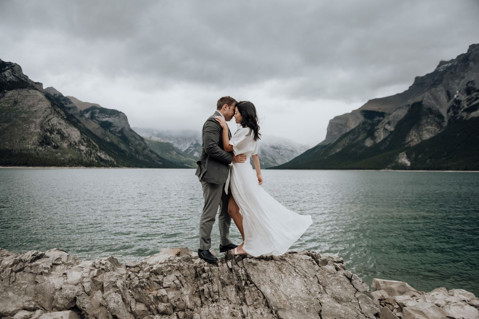 couple kissing at lake minnewanka