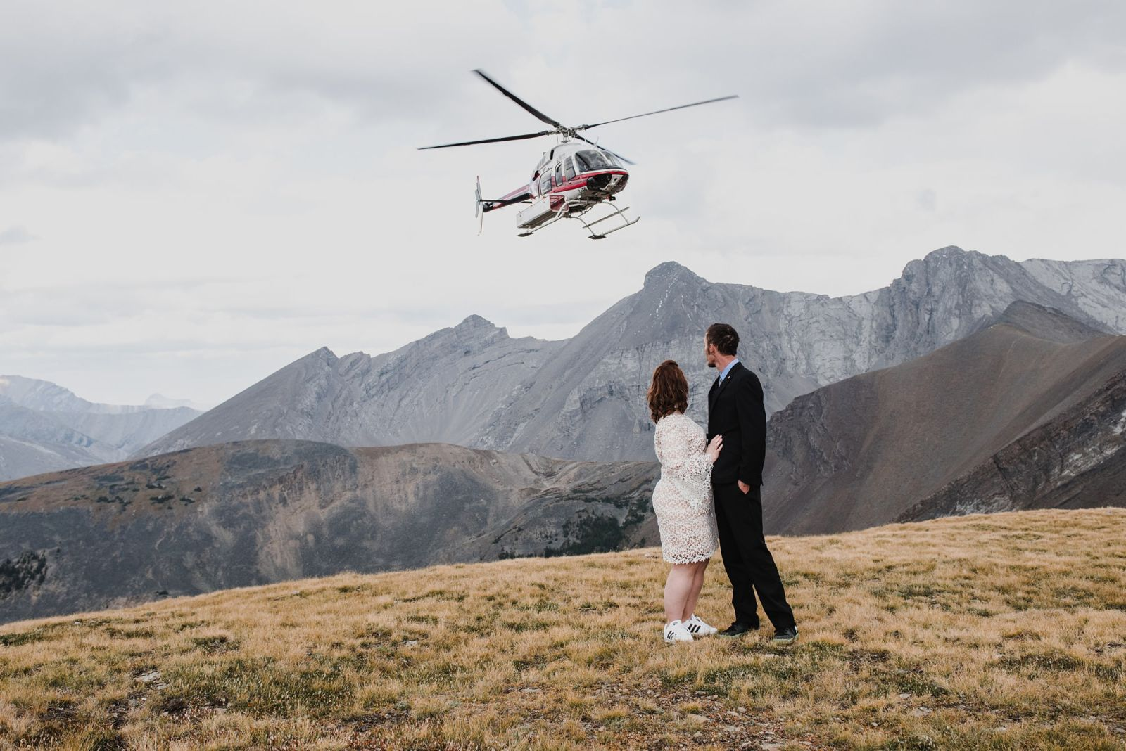 casual bride and groom on mountain with helicopter for wedding