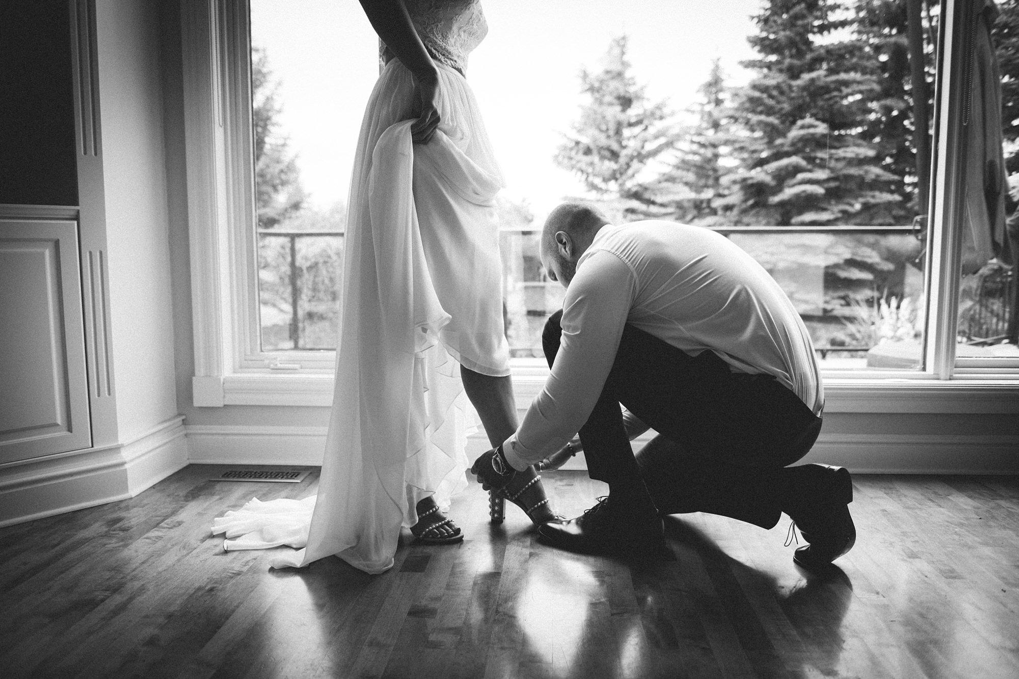Bride getting shoe done by groomsman in backyard wedding in calgary