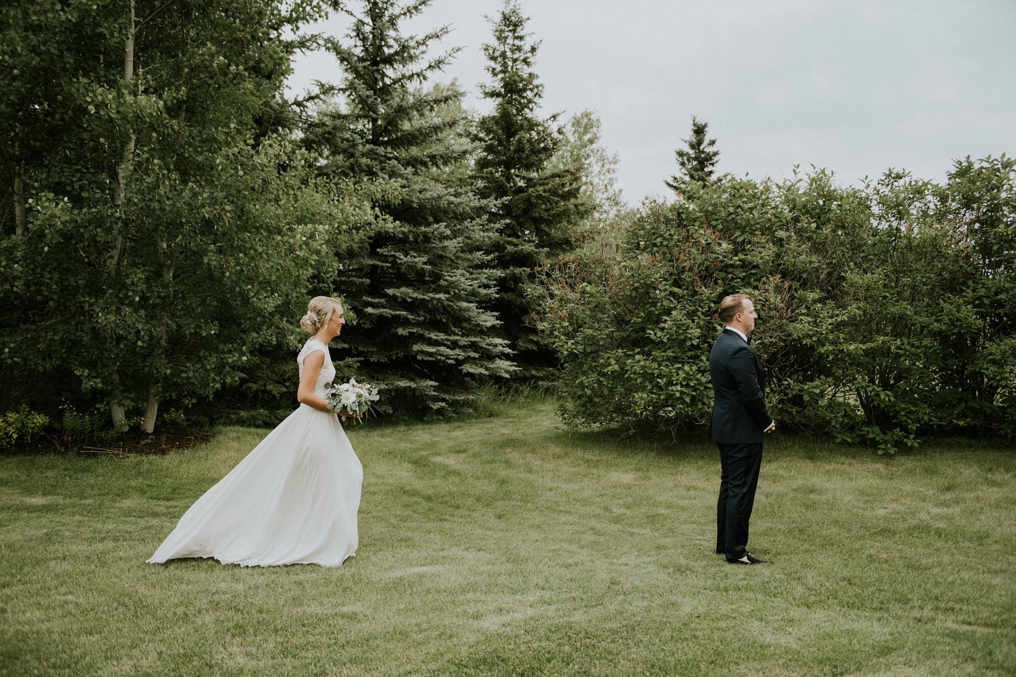 bride and groom first look images in calgary backyard wedding