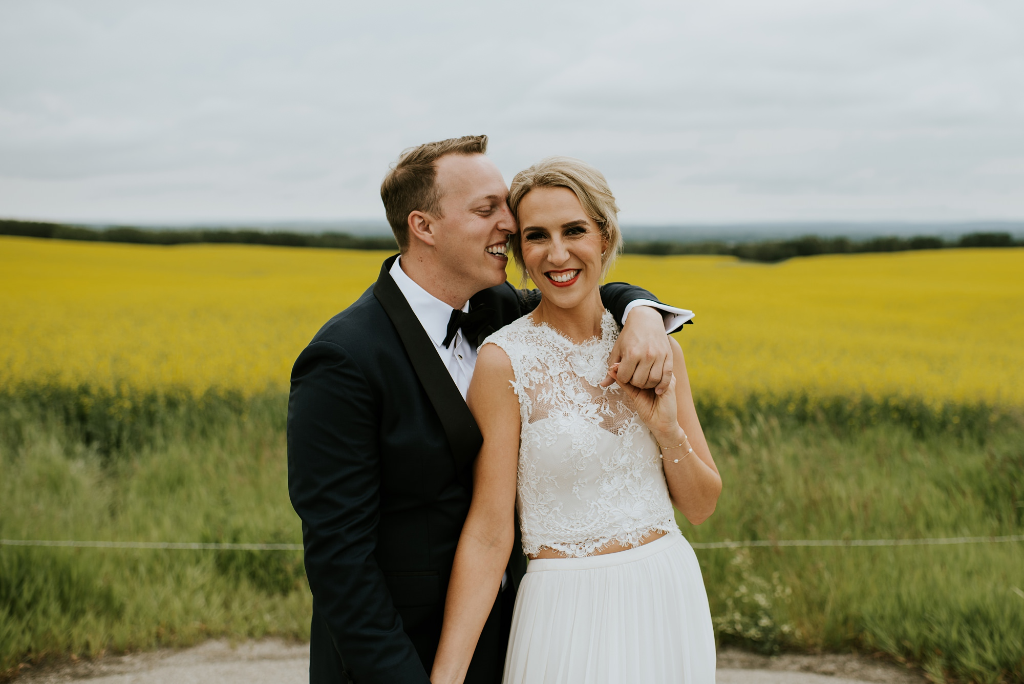 bride and groom embracing in front of canola field in alloy restaurant wedding
