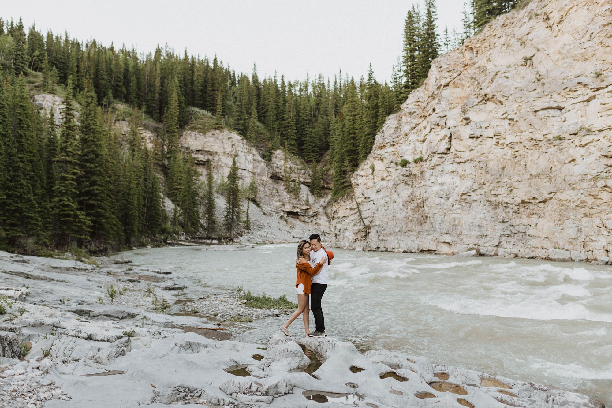 engaged couple embracing with mountains at elbow falls engagement session