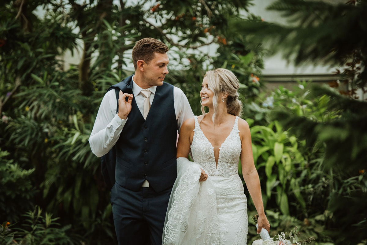 bride and groom walking in indoor garden at calgary zoo wedding