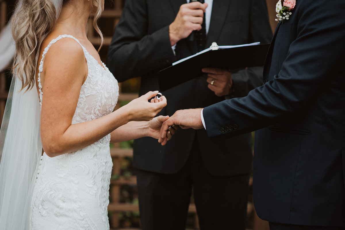bride holding ring in outdoor wedding ceremony