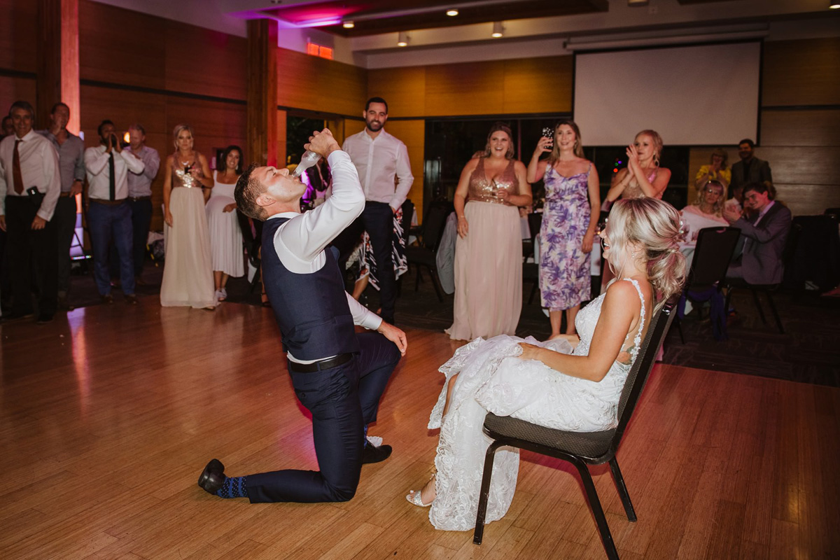 groom taking shots at wedding reception