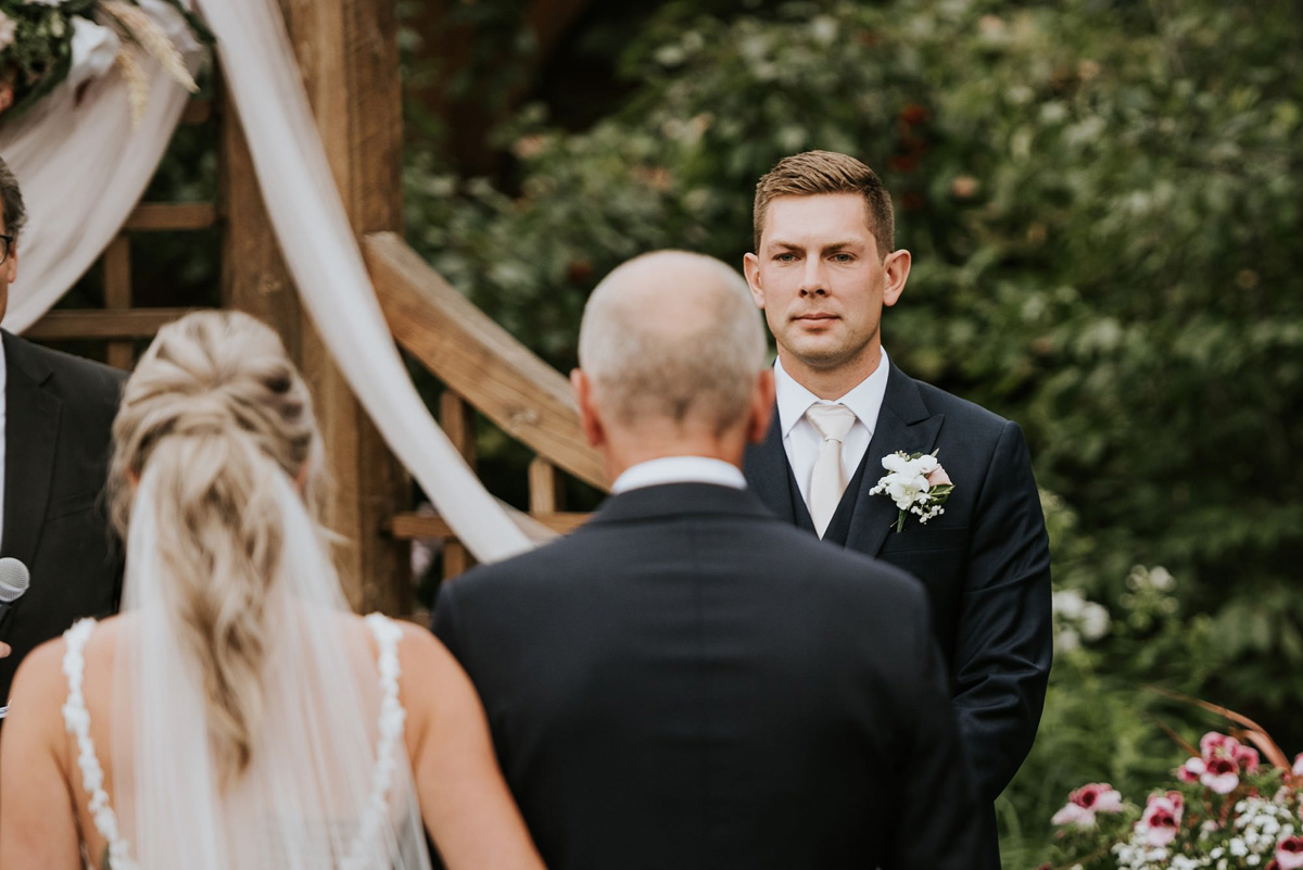 groom reaction to bride at outdoor wedding ceremony