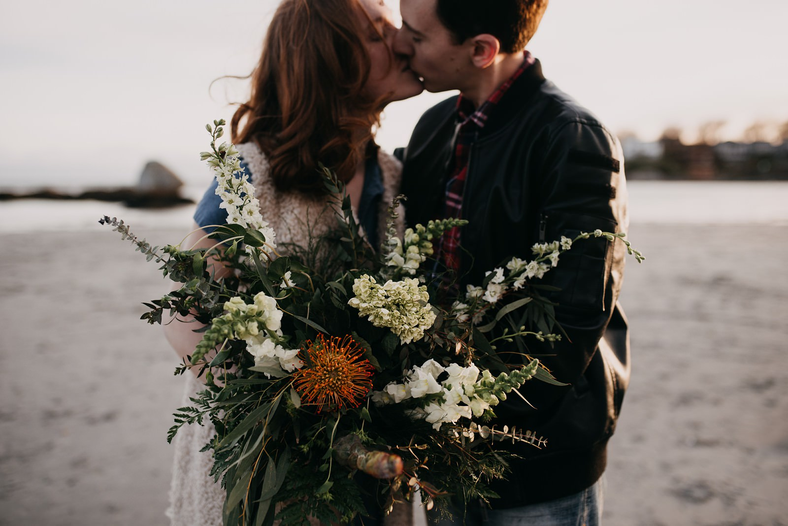 couple kissing on beach with wedding bouquet