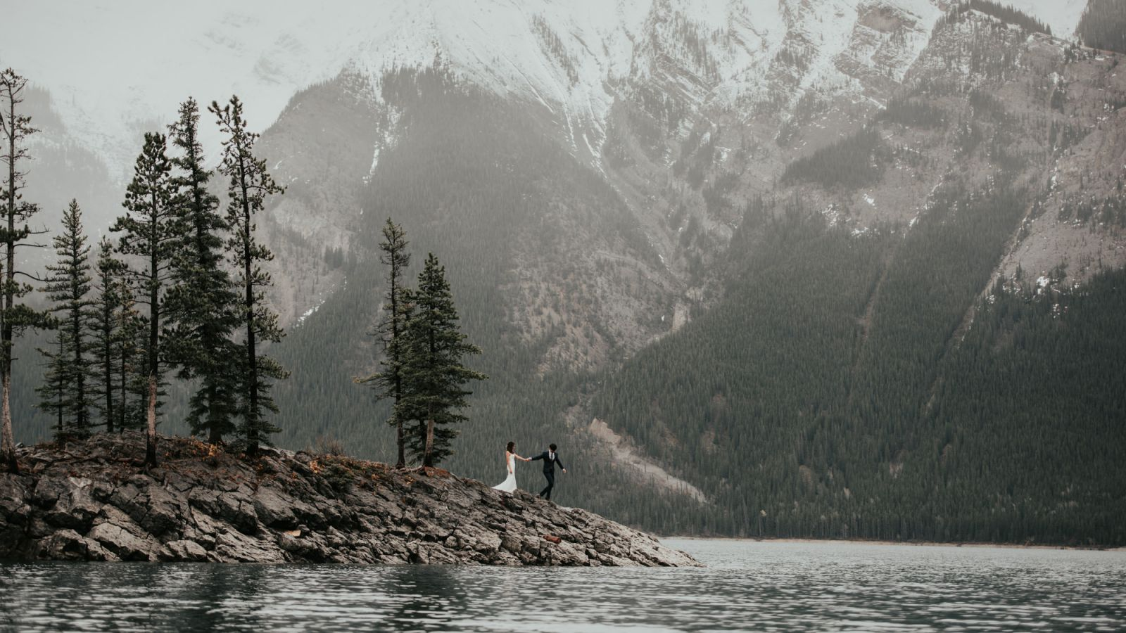 bride and groom walking on rocks at lake minnewanka