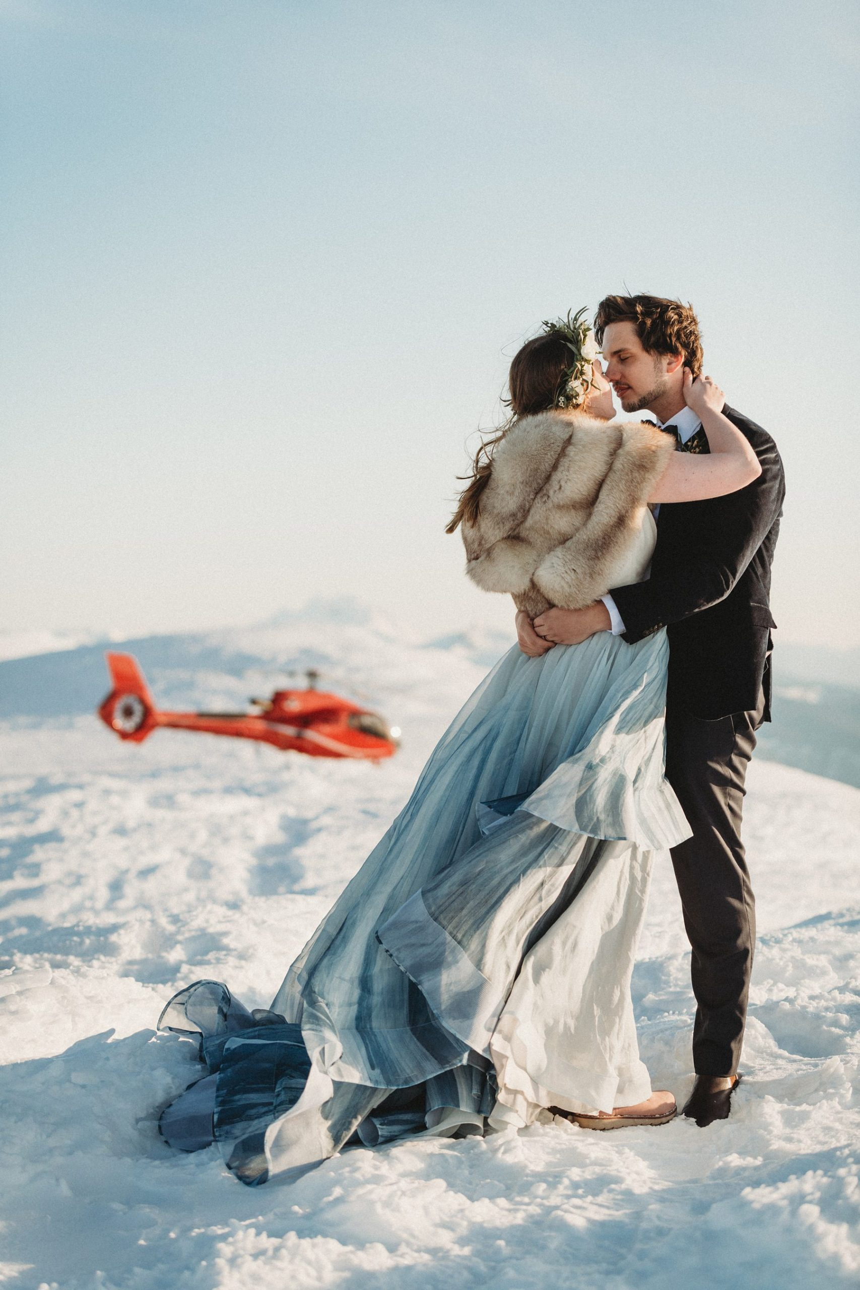 bride and groom and helicopter on mountains