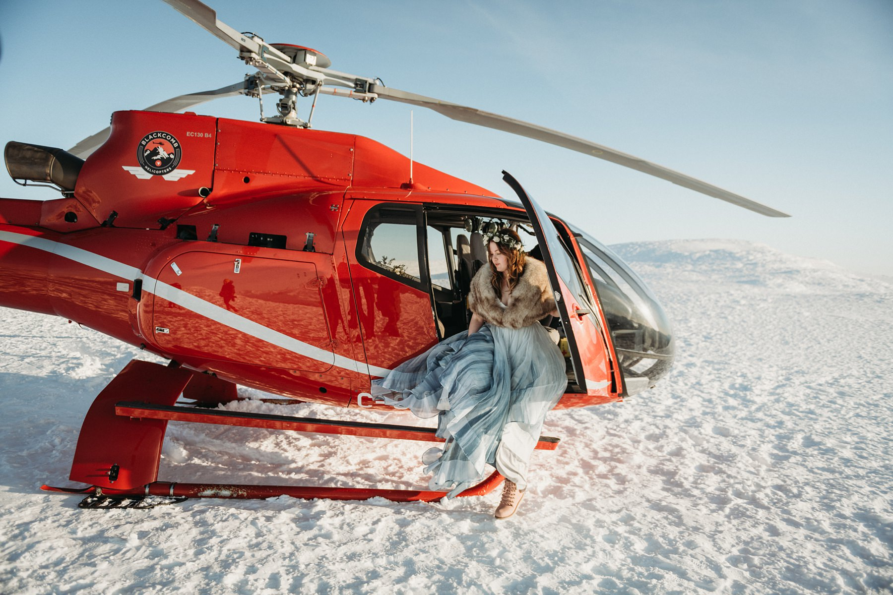 bride walking out of helicopter on mountain top