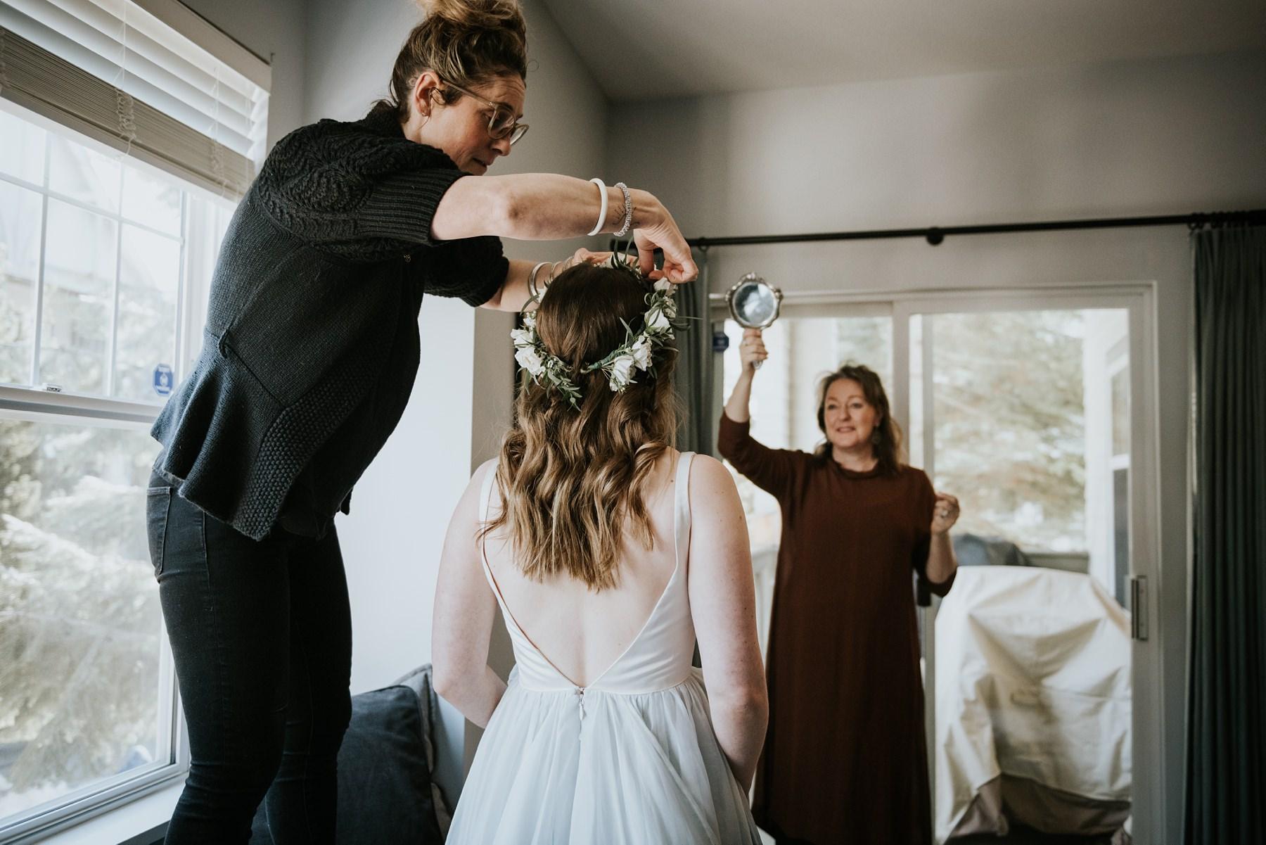 bride putting on flower crown for winter wedding in whistler