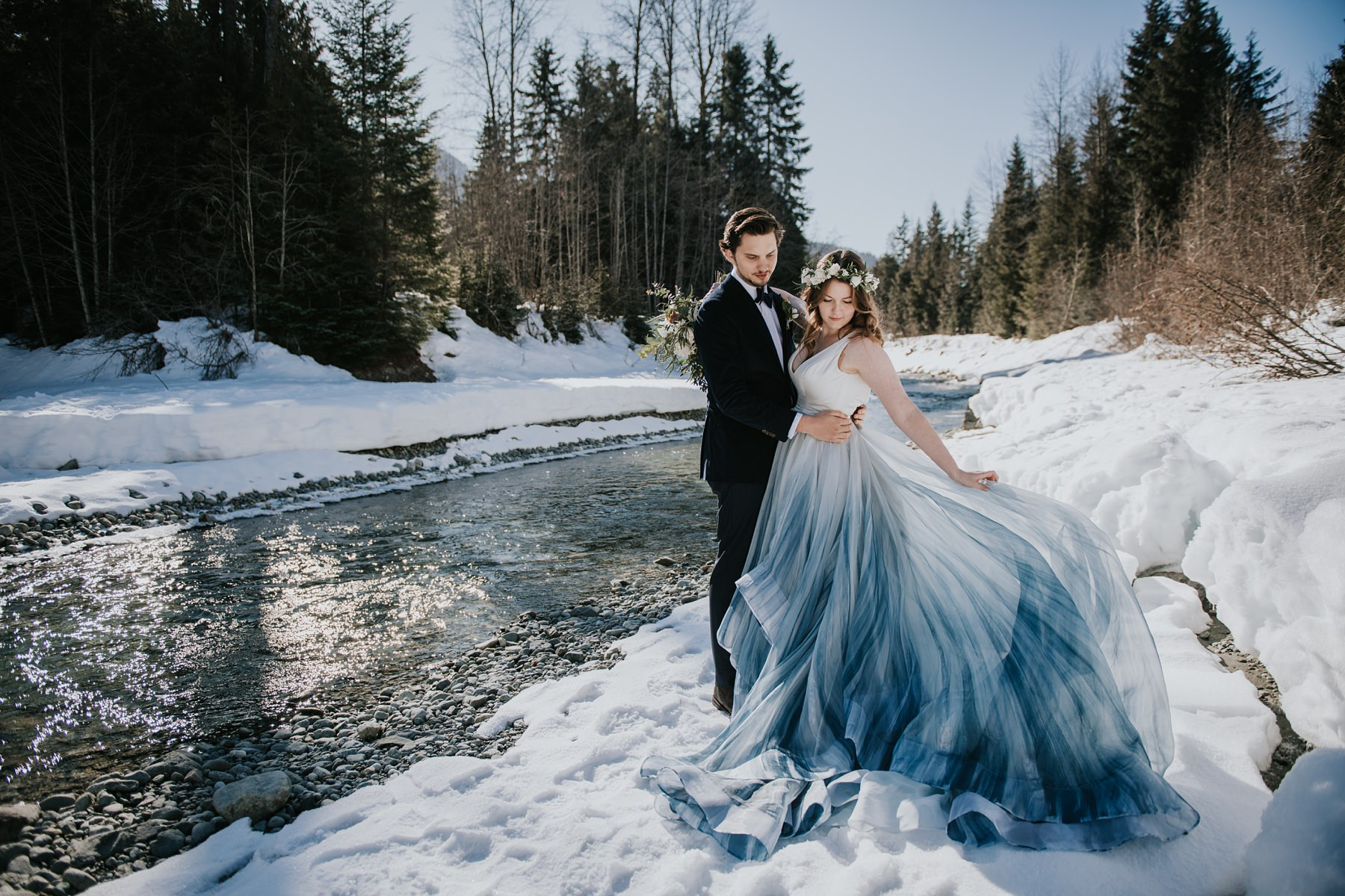 bride and groom at river in winter