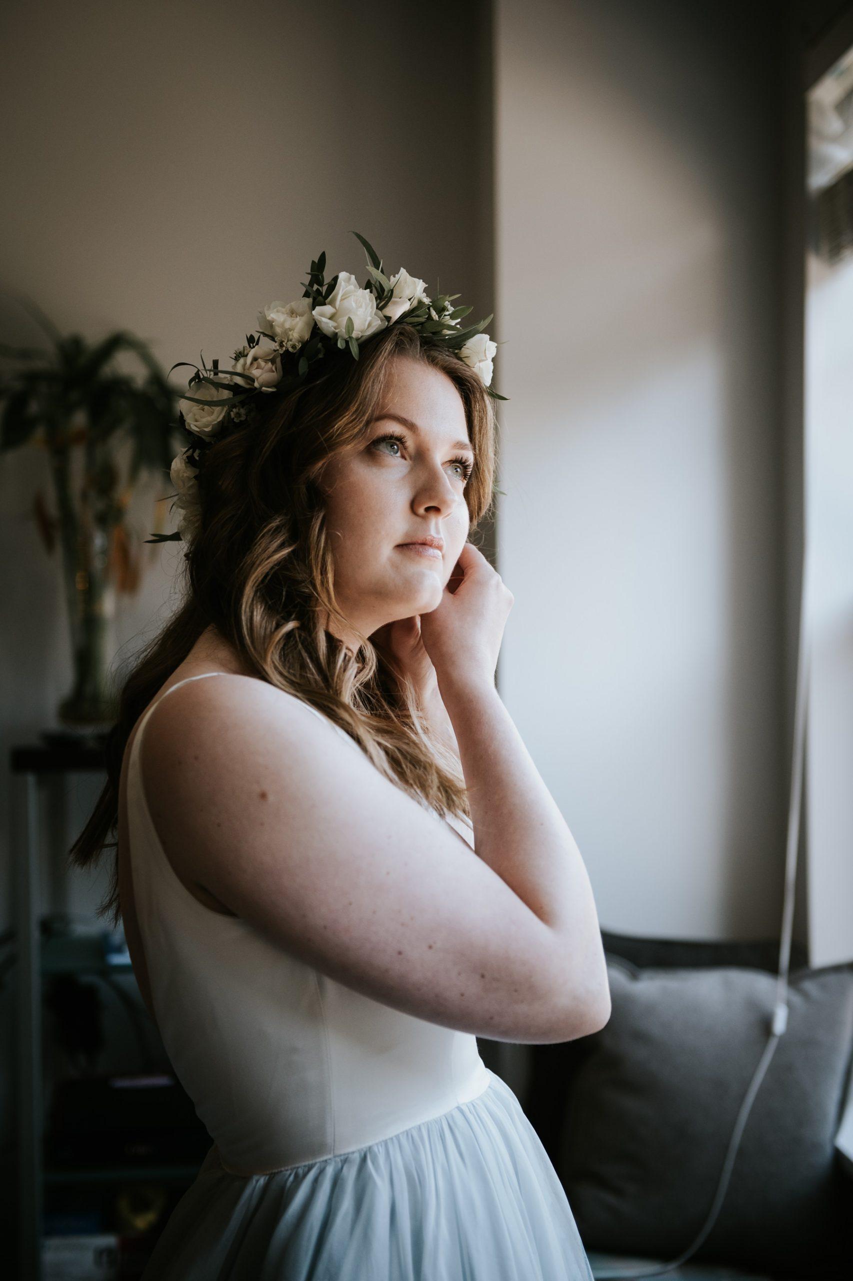 bride putting on earrings for winter Nita lake lodge wedding