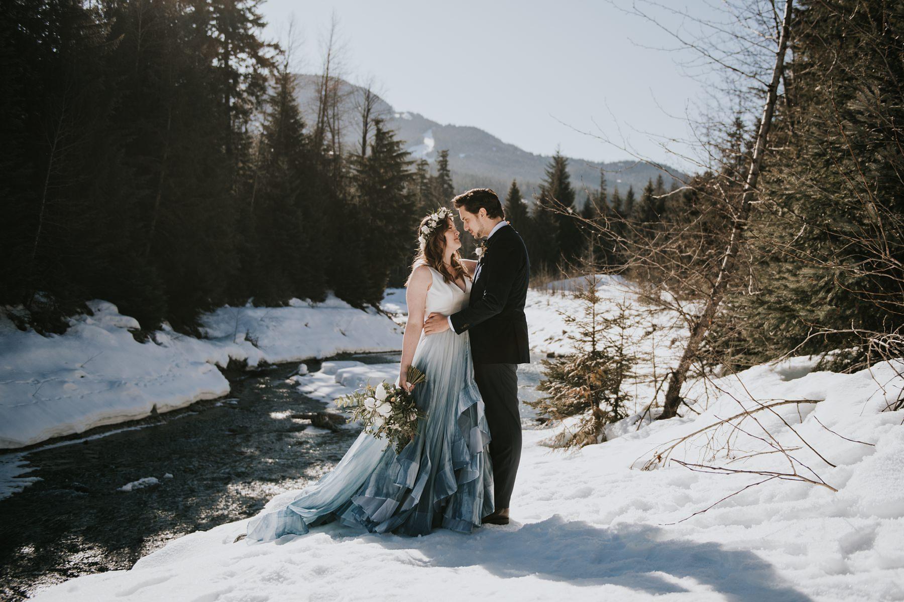 bride and groom embracing in the snow at the river at Nita lake lodge wedding
