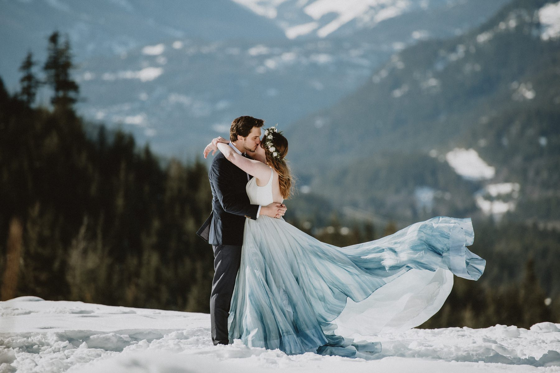 bride and groom kissing on mountain top in whistler
