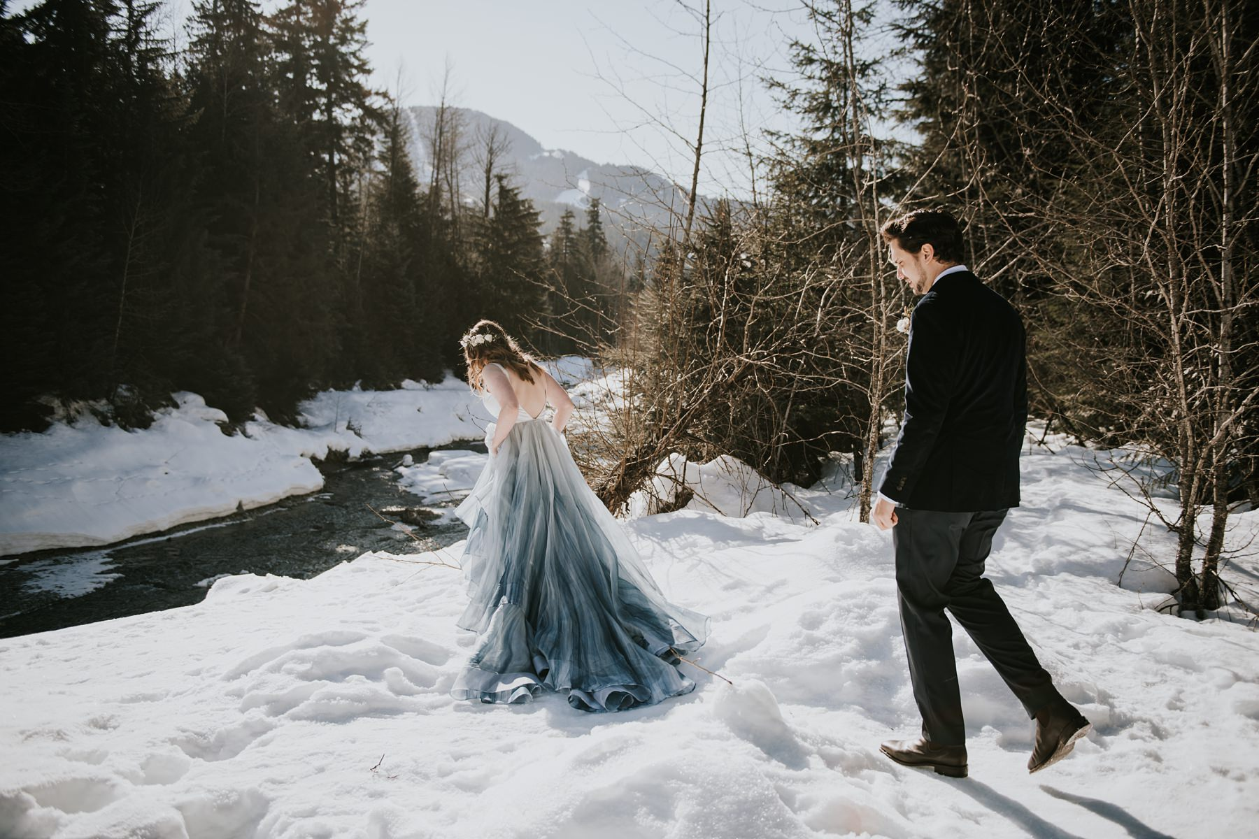 bride and groom walking in snow in whistler