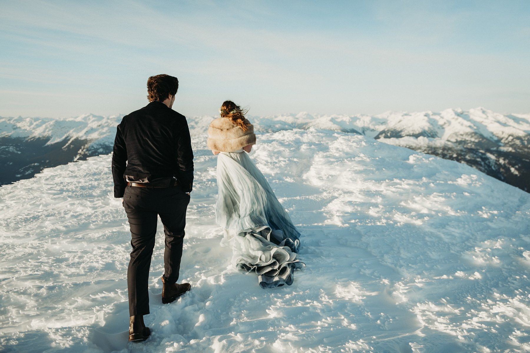 bride and groom walking in snow on mountaintop with backcomb helicopters