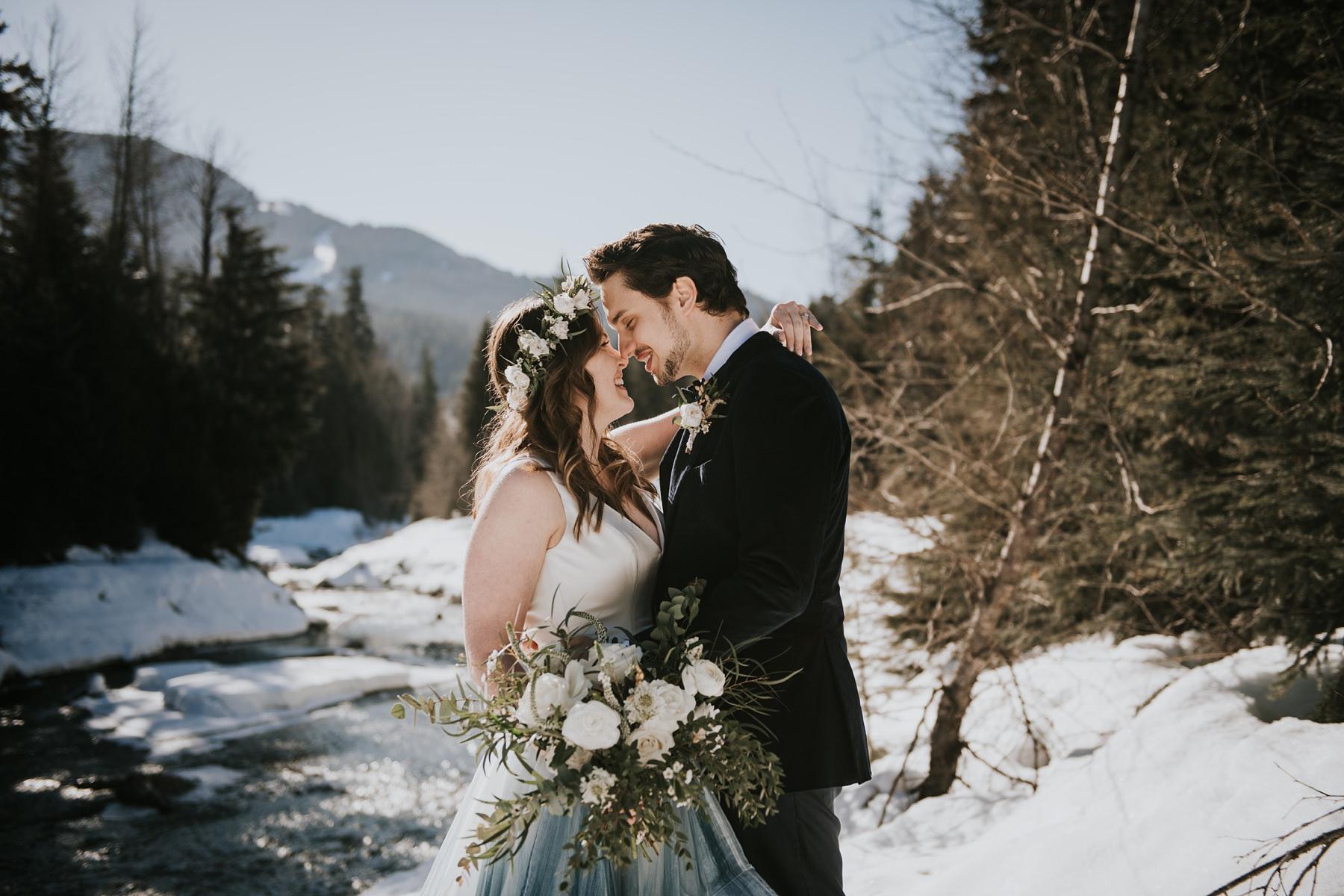 bride and groom embracing at the river at winter Nita lake lodge wedding