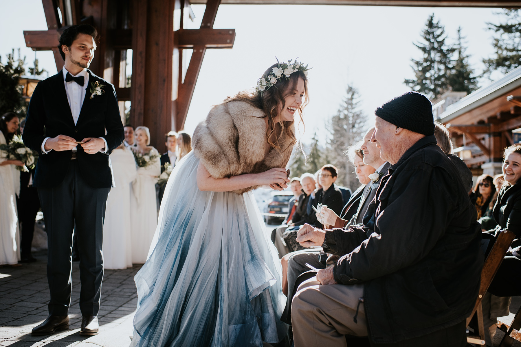 bride laughing with guests at outdoor wedding ceremony
