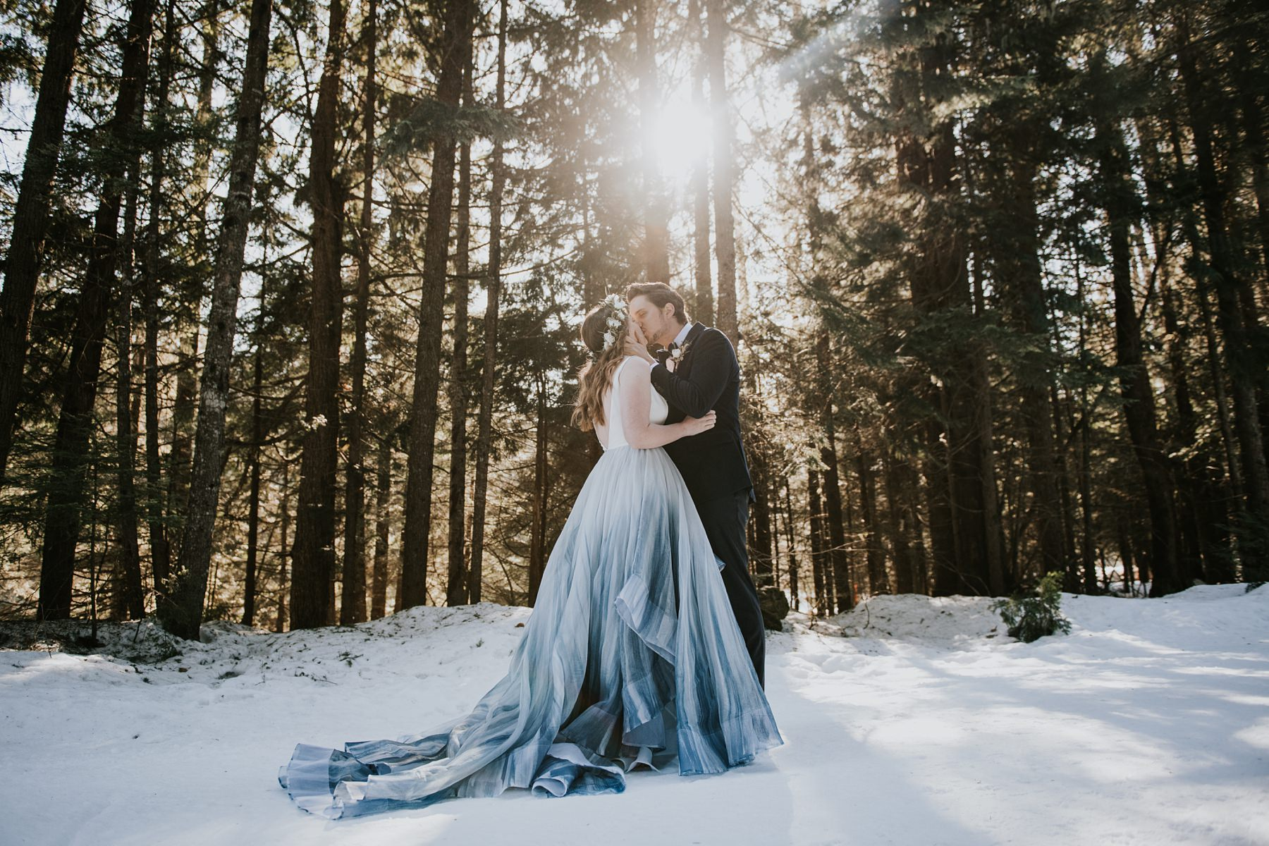 bride and groom kiss in forest during winter wedding