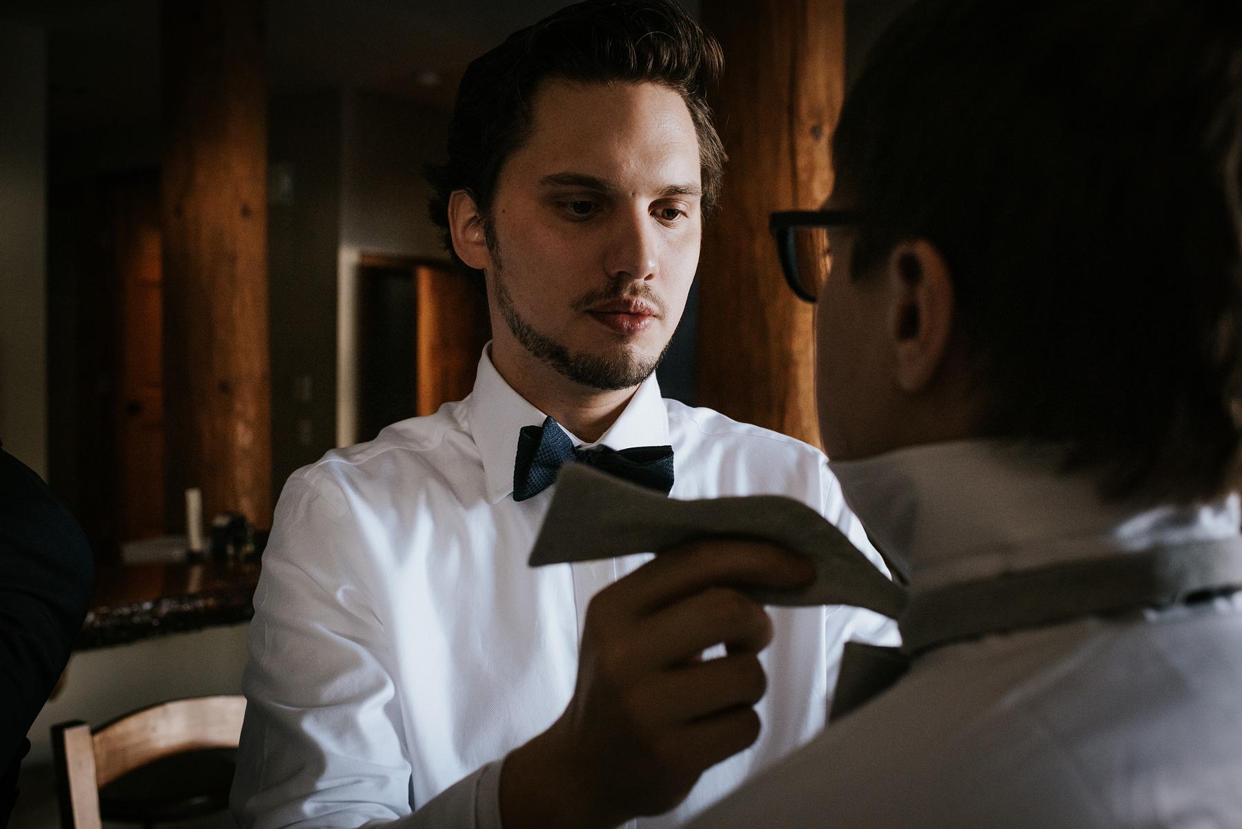 groom helping groomsmen get ready for whistler winter wedding